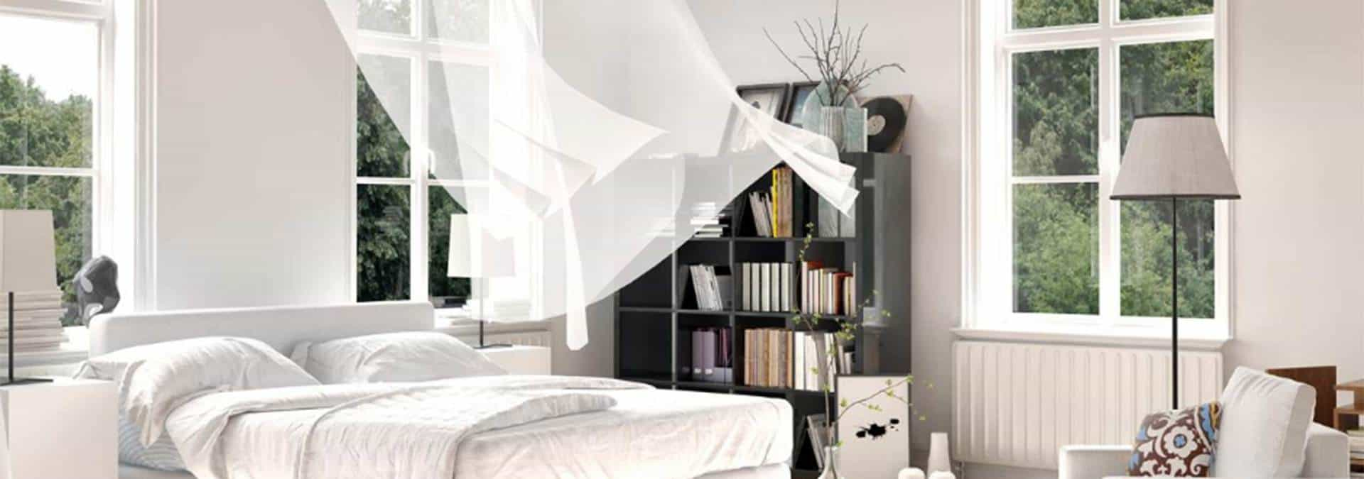 Bedroom with open window and fresh air blowing in
